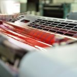 Image of process magenta ink in the fountains and on the rollers of a offset color printing press.