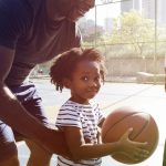 father and daughter play basketball